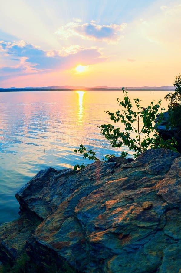 夏天日落风景-日落光和湖的点燃的边缘石峭壁 五颜六色的夏天风景场面 免版税库存图片