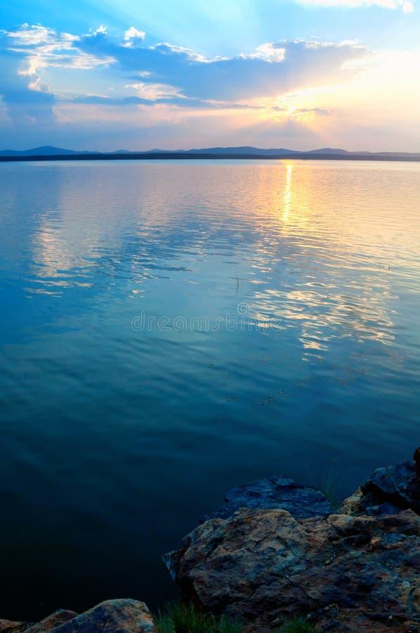 夏天日落风景-石冷的平衡的光点燃的峭壁和湖 剧烈的夏天风景 免版税库存照片