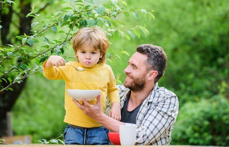 夏天早餐健康食品概念 哺养的婴孩 孩子的菜单 E 父亲儿子吃食物 免版税库存照片