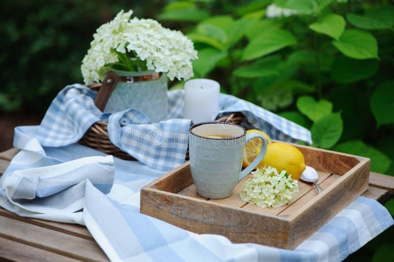 夏天早餐在美丽的开花的庭院里 茶用柠檬,八仙花属在木桌上开花 免版税库存照片
