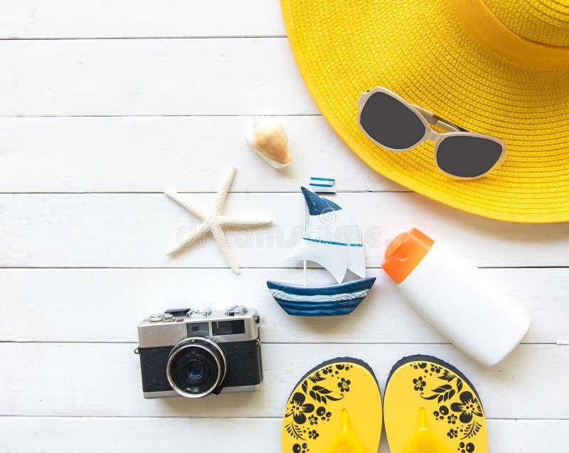 夏天时尚妇女黄色大帽子和辅助部件在海滩 热带的海运 异常的顶视图,木白色背景 免版税库存照片