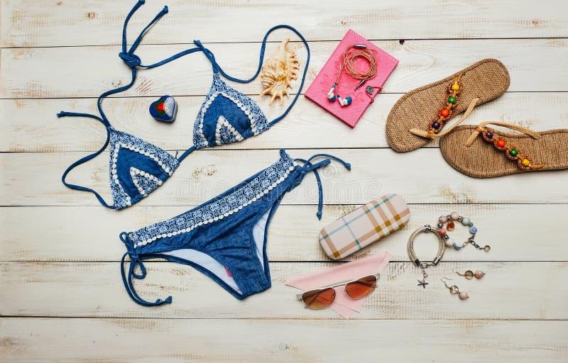 夏天时尚平的位置与蓝色比基尼泳装泳装和女孩辅助部件的在白色木背景 免版税图库摄影