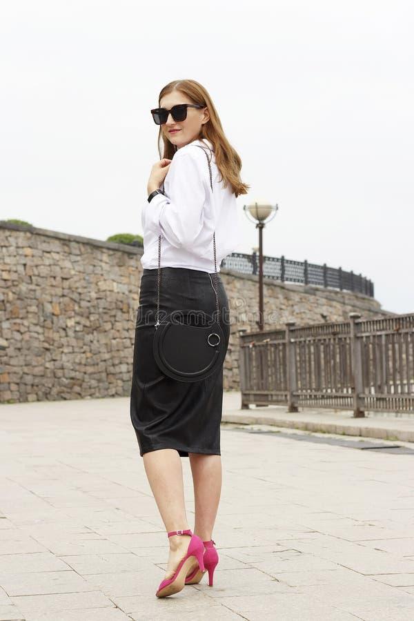 夏天时尚成套装备 白色女衬衫、裙子和时髦的桃红色凉鞋步行的女孩在街道下 免版税库存照片