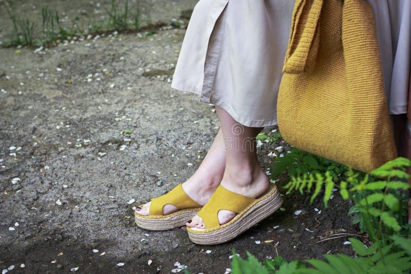 夏天时尚成套装备 礼服、黄色鞋子和时髦被编织的袋子的,侧视图女孩 免版税图库摄影