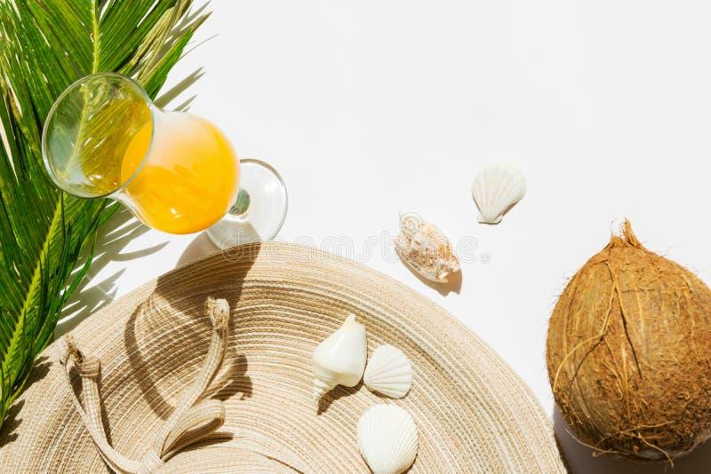 夏天时尚热带假期旅行概念妇女的海滩装草帽椰子果汁绿色棕榈叶鸡尾酒杯  免版税图库摄影