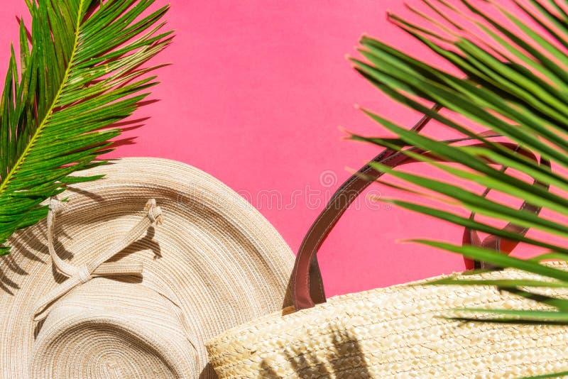 夏天时尚热带假期概念 在紫红色的桃红色的妇女的女性海滩装草帽柳条袋子绿色棕榈叶 免版税库存图片