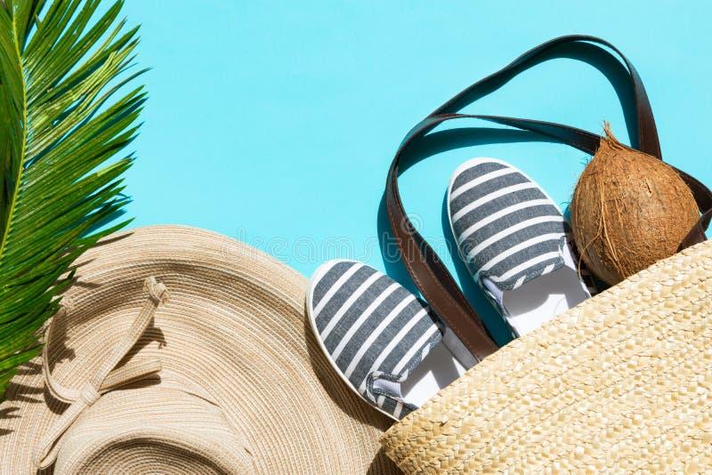 夏天时尚热带概念 妇女的女性海滩装草帽柳条袋子帆布镶边鞋子椰子绿色棕榈叶 库存照片