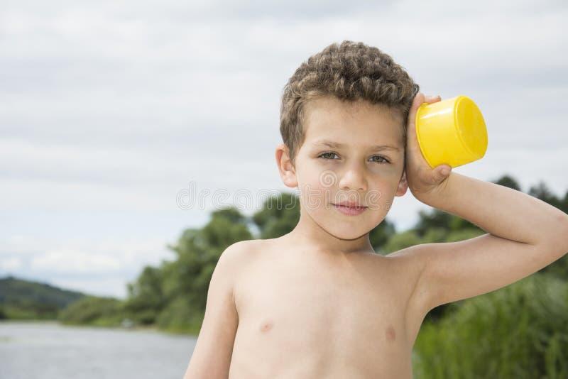 夏天明亮的晴天一个卷曲男孩在海滩站立在r附近 库存照片