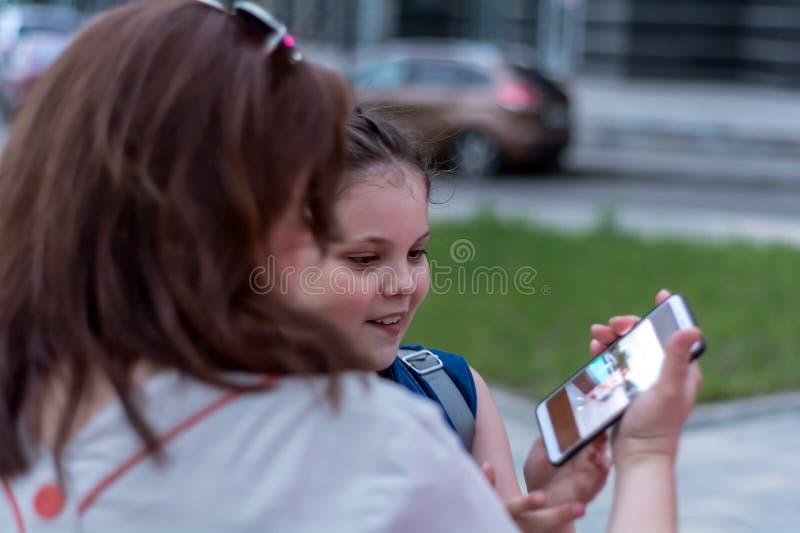 夏天晚上 ?? 在智能手机的母亲和女儿手表好的照片 图库摄影