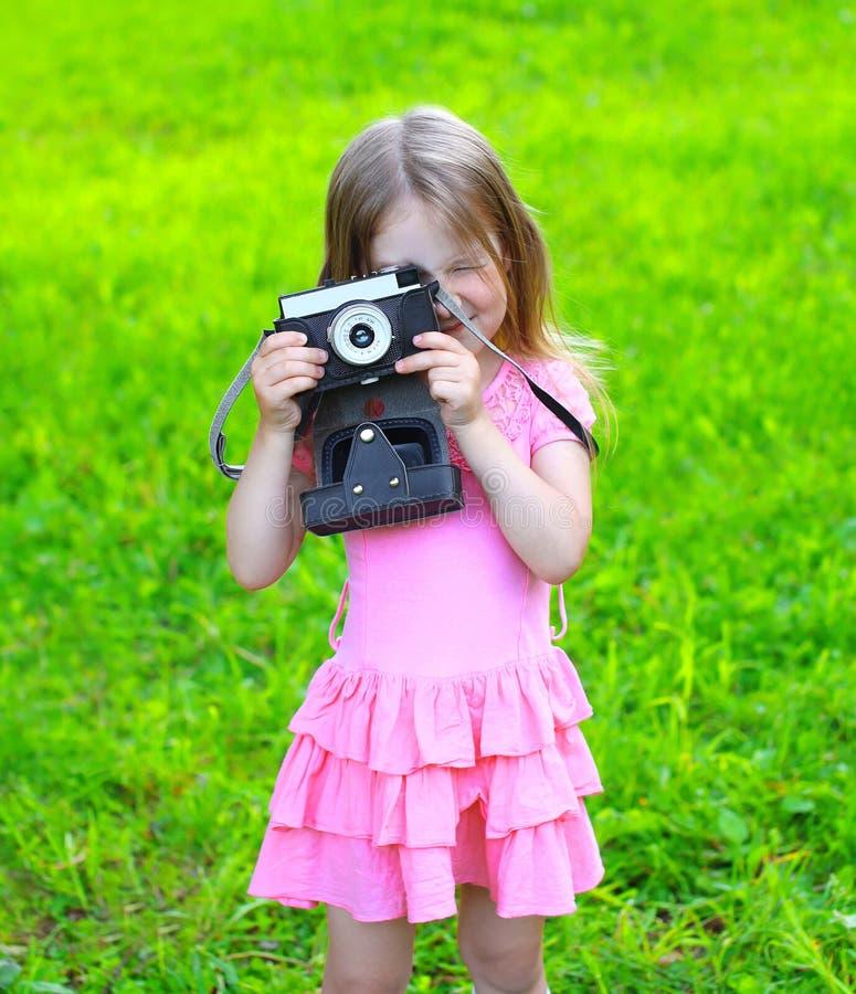 夏天有获得老减速火箭的葡萄酒的照相机的画象孩子乐趣 免版税图库摄影