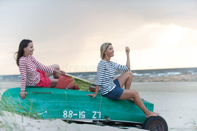 夏天有风海岸的两年轻女人冥想风雨如磐的波浪的 免版税库存照片