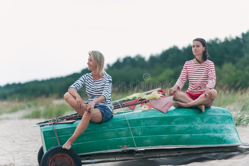 夏天有风海岸的两年轻女人冥想风雨如磐的波浪的 免版税库存图片