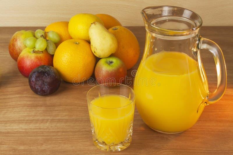 夏天果汁的生产 在一个玻璃瓶子的国内新鲜的橙汁在一张木桌上 免版税库存照片