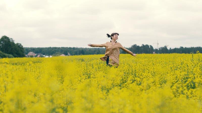 夏天步行的快乐的少妇在花田 库存照片
