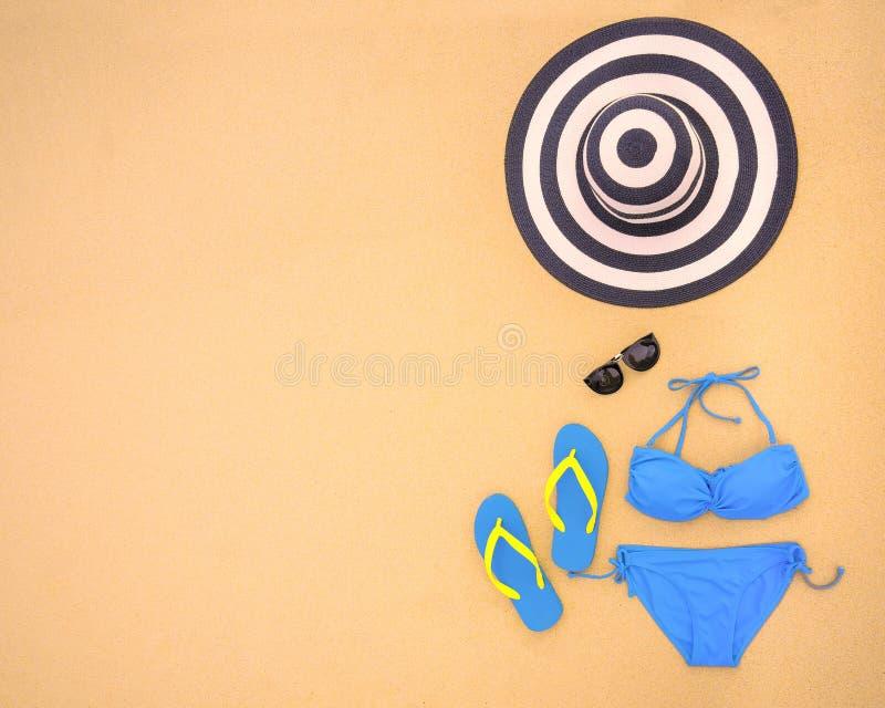 夏天比基尼泳装和辅助部件时髦的海滩集合,海滩比基尼泳装夏天成套装备和海沙作为背景,顶视图,概念 图库摄影