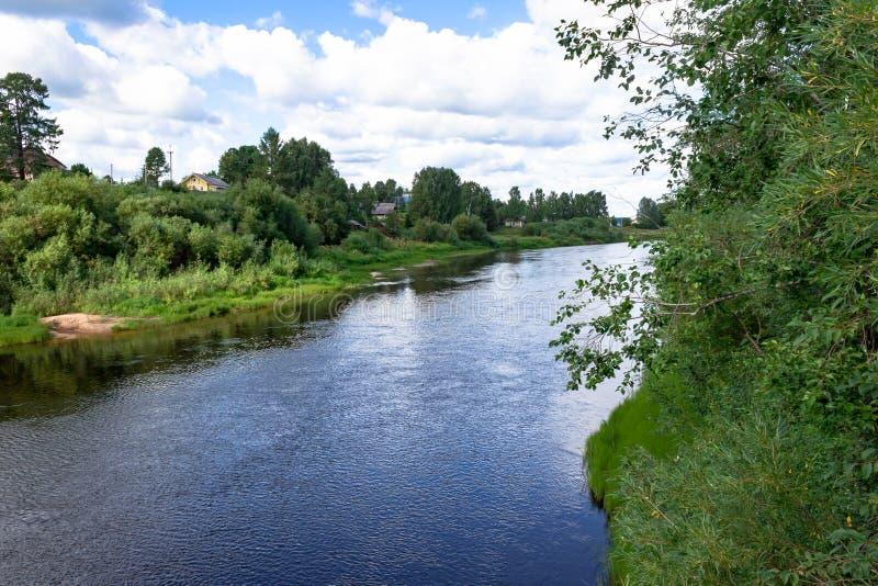 夏天河村庄风景 在银行、绿草和树蓝色河和多云天空的沙滩 库存图片