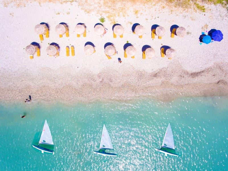 夏天海滩在有的阳伞和的sunbeds的莱夫卡斯州希腊 免版税库存照片