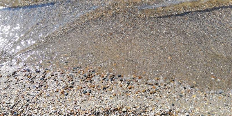 夏天海背景 在沙滩的透明海波浪卷 库存照片