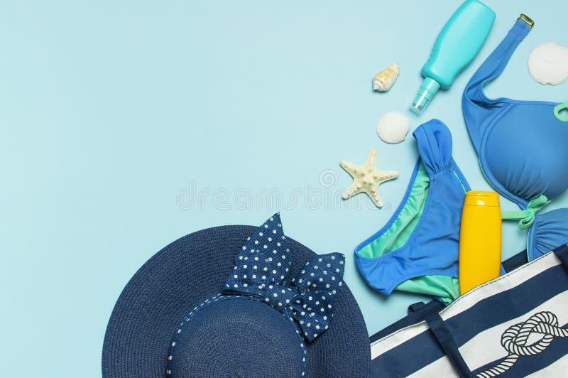夏天海辅助部件 在蓝色的海滩袋子珊瑚触发器泳装女性草帽壳海星遮光剂瓶身体浪花 免版税库存照片