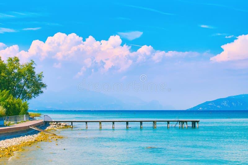 夏天湖加尔达美好的风景视图在意大利与绿松石水和惊人的桃红色晚上覆盖 免版税库存图片