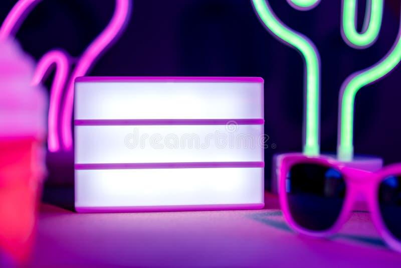 夏天灯箱火鸟、仙人掌、太阳镜和空白的灯箱有霓虹桃红色和蓝色光的在桌上与monstera叶子 ?? 免版税库存图片