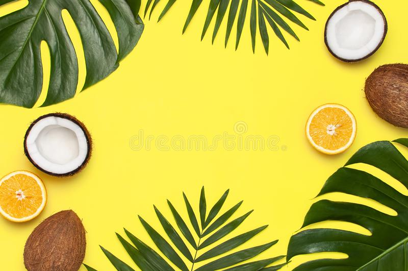 夏天热带构成 棕榈树和monstera,椰子绿色热带叶子框架,橙色在明亮的黄色 图库摄影