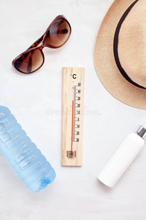 夏天热的根本辅助部件:太阳镜,帽子,遮光剂,瓶水 平的位置,顶视图 免版税图库摄影