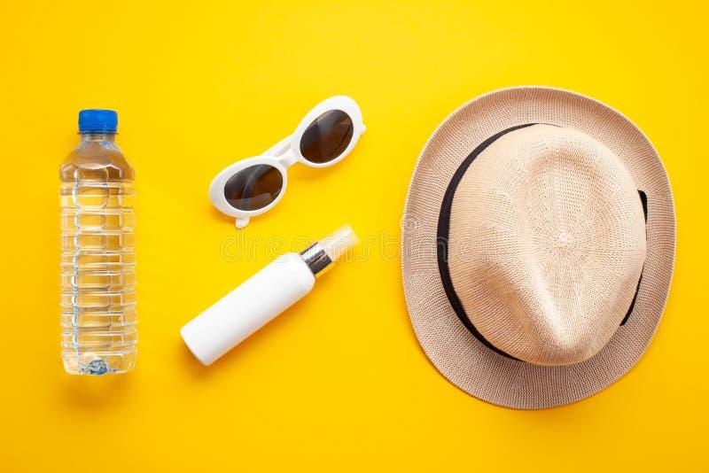 夏天热的根本辅助部件:太阳镜,帽子,遮光剂,瓶水 平的位置,顶视图 库存照片