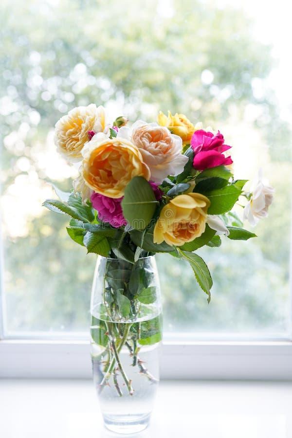 夏天玫瑰花束在玻璃花瓶的在窗口附近 花背景,贺卡 图库摄影