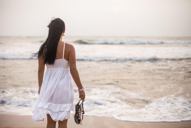 夏天白色礼服身分在海滩和看的年轻深色的妇女对海 放松在度假的女孩 库存图片
