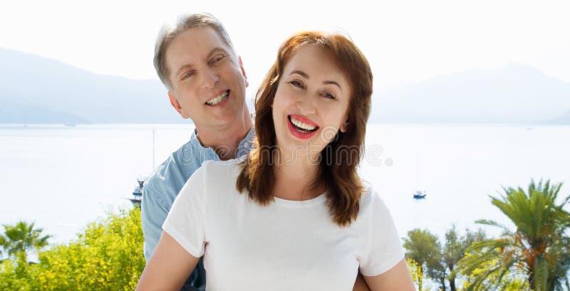 夏天白色T恤杉模板 愉快的中间年迈的家庭夫妇假期 海滩和假日概念 r 免版税库存照片