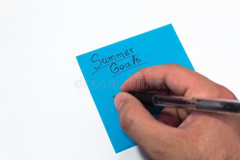 夏天目标 拿着一支黑笔的手写下计划在假期 免版税库存照片
