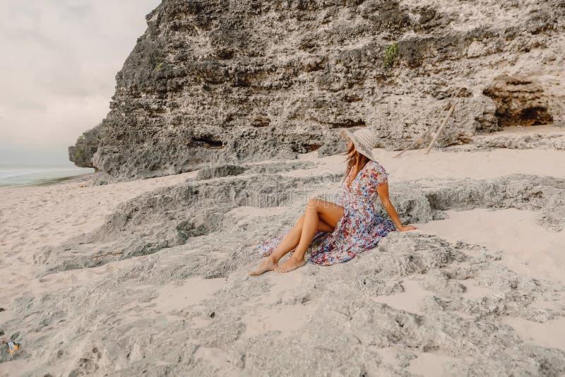夏天礼服的时髦的妇女坐海滩 女性样式假期 免版税库存照片
