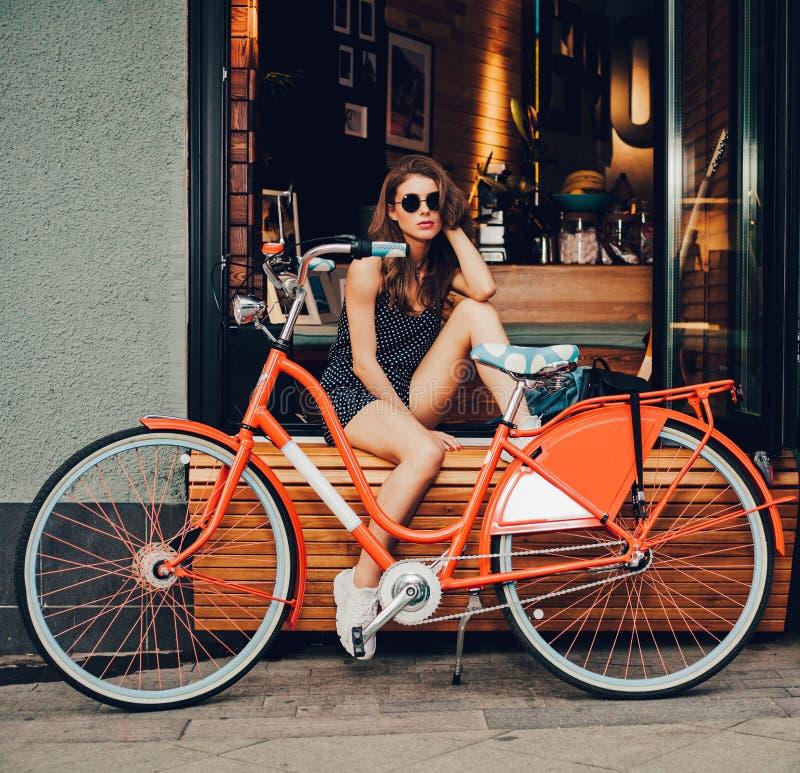 夏天礼服的逗人喜爱的女孩坐与红色葡萄酒自行车在欧洲城市 晴朗的夏天 好的女孩 图库摄影