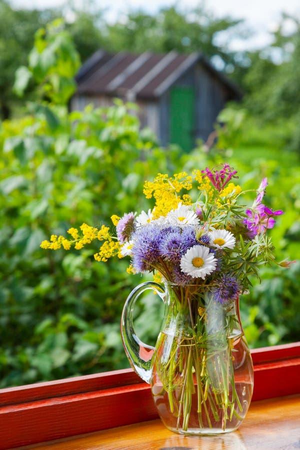 夏天花和医治草本花束在水罐 图库摄影