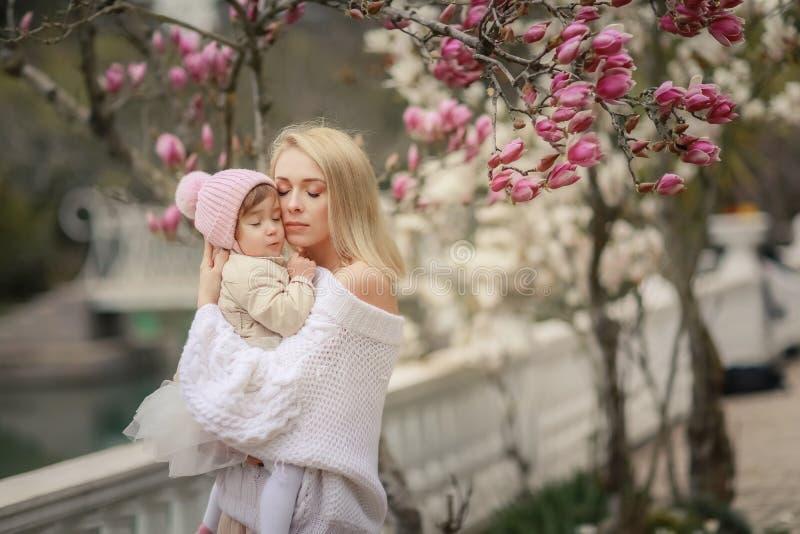 夏天草甸的幸福家庭 女孩儿童拥抱和亲吻母亲的小女儿 库存照片