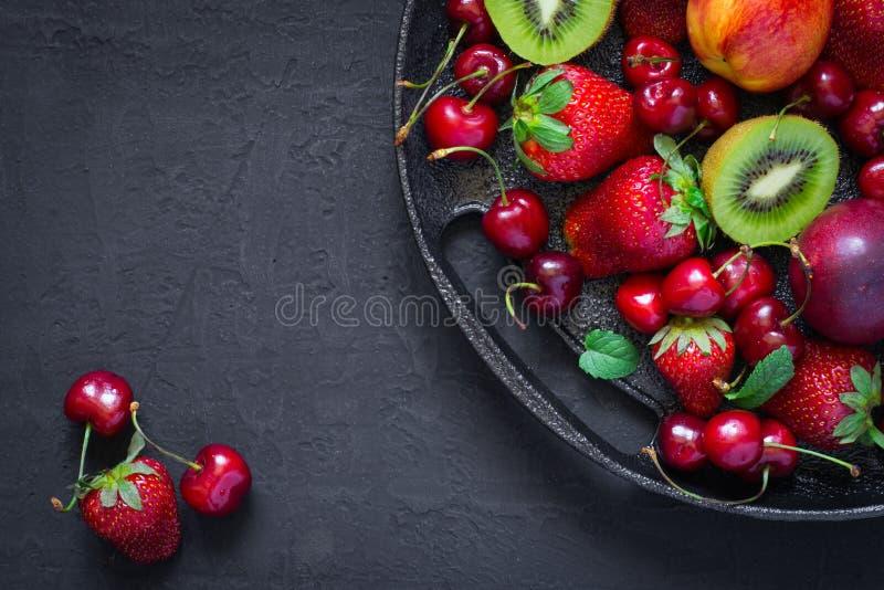 夏天莓果和果子的混合在一个黑色的盘子 顶视图与 免版税库存照片
