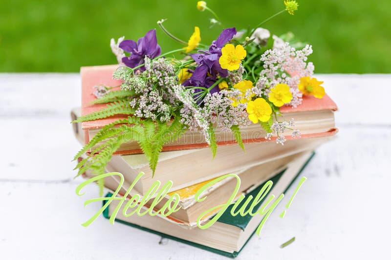 夏天葡萄酒构成 旧书,野花花束在土气背景的 说明:你好7月 库存图片