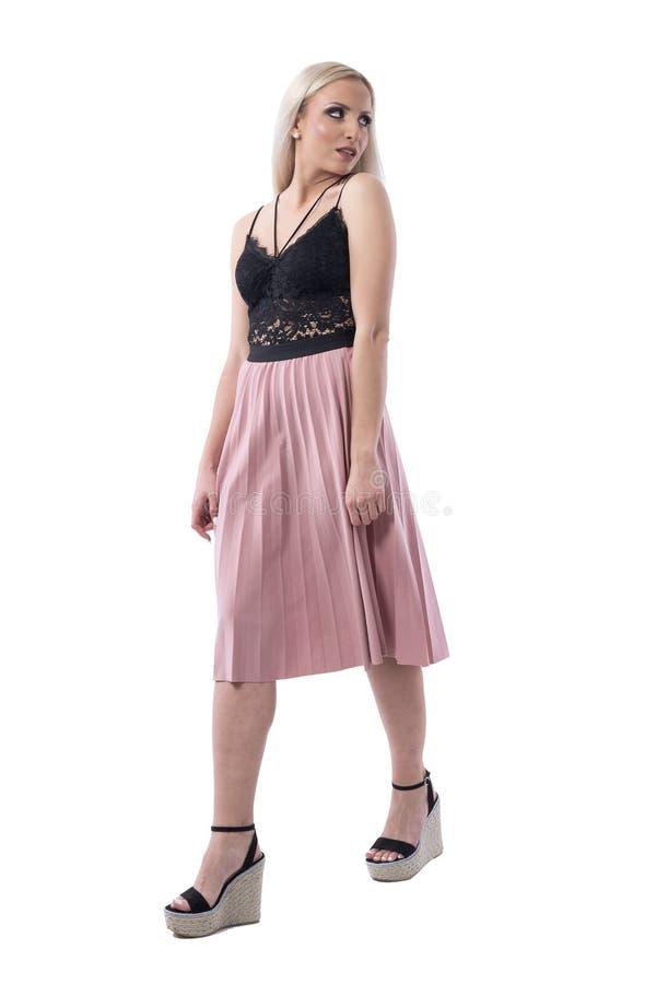 夏天衣裳的年轻性感的白肤金发的妇女走和回顾在肩膀的 免版税库存照片