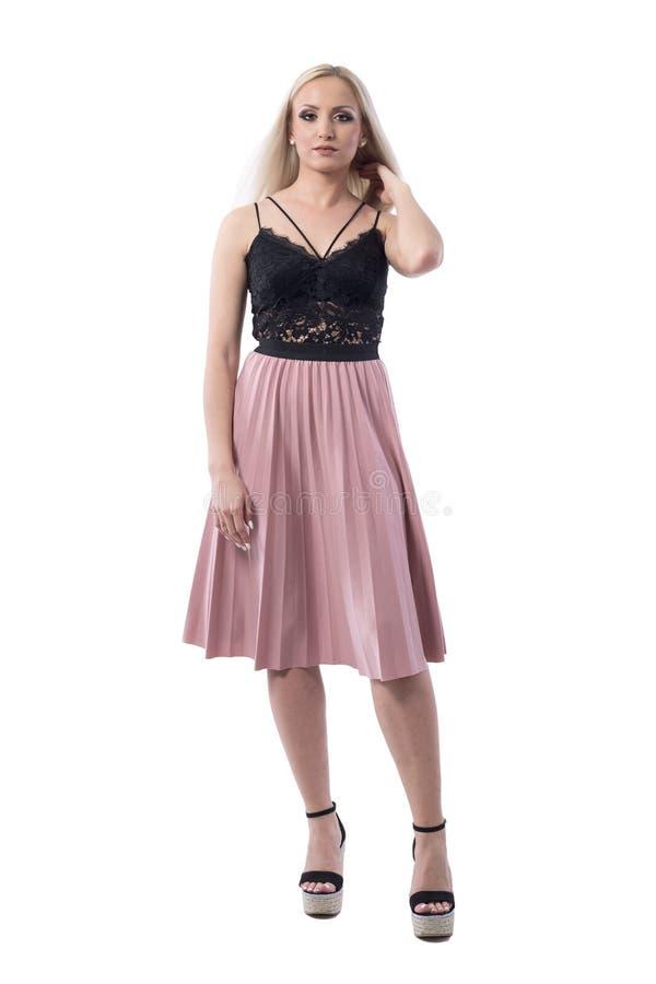 夏天裙子的确信的年轻时髦的白肤金发的妇女和系带看照相机的顶面感人的头发 库存图片