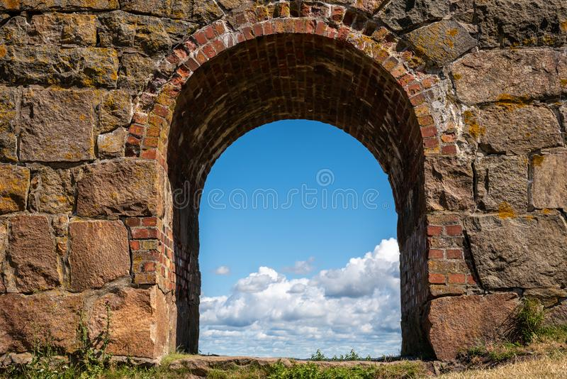夏天视图通过在瓦尔贝里堡垒的一个老中世纪石墙被成拱形的门在有蓝色多云天空的瑞典在背景中 免版税库存图片