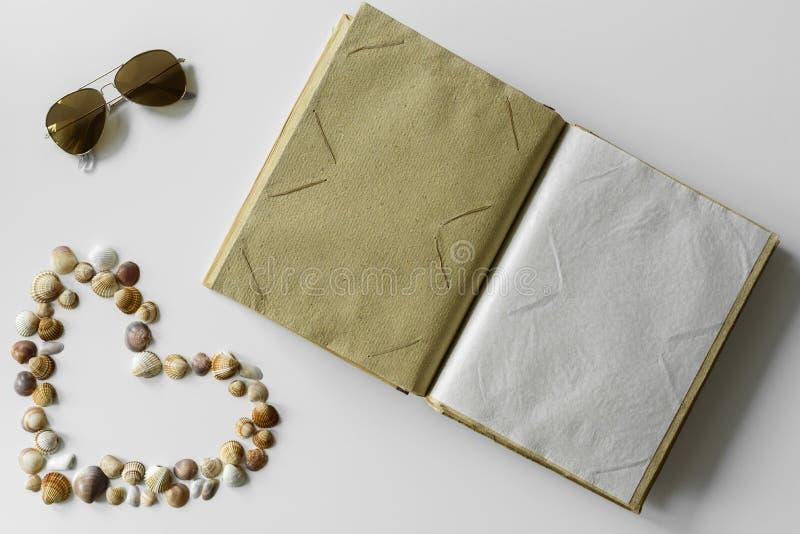 夏天设定了-贝壳心脏、太阳镜和象册 免版税库存照片