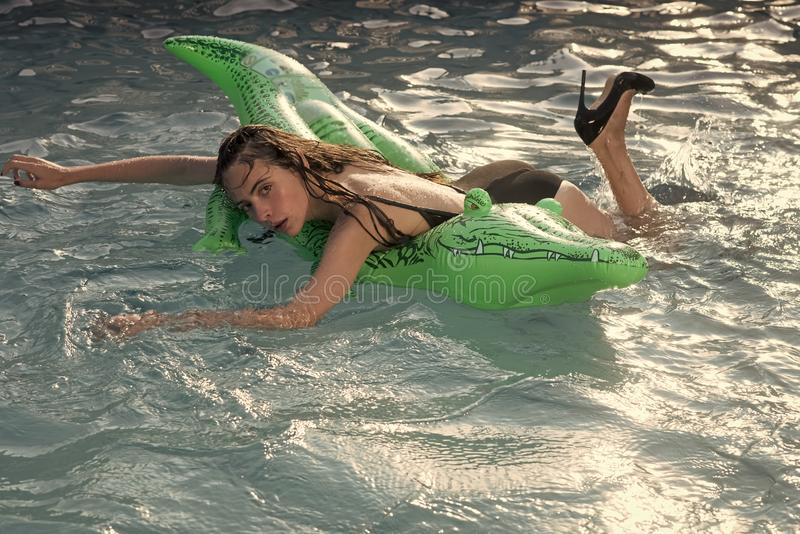 夏天说谎在游泳池的气垫的一名美丽的妇女的休息画象 免版税库存照片