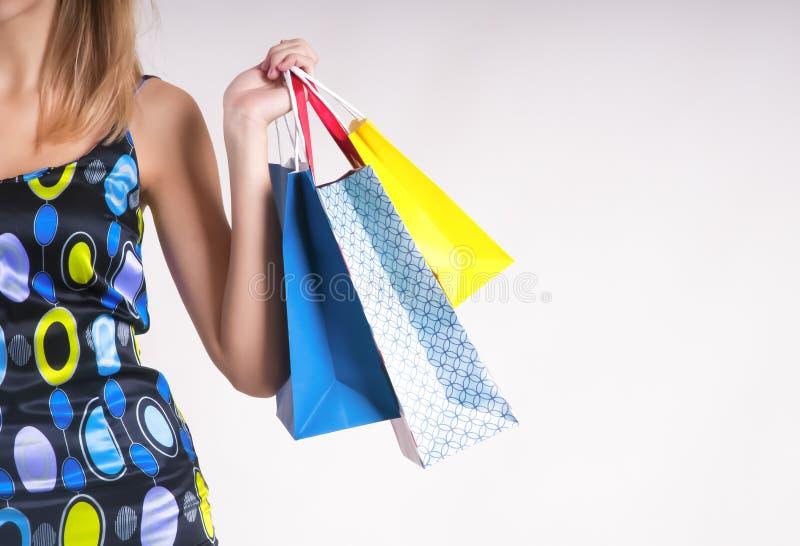 夏天购物的少妇与在灰色背景的购物袋 免版税库存照片