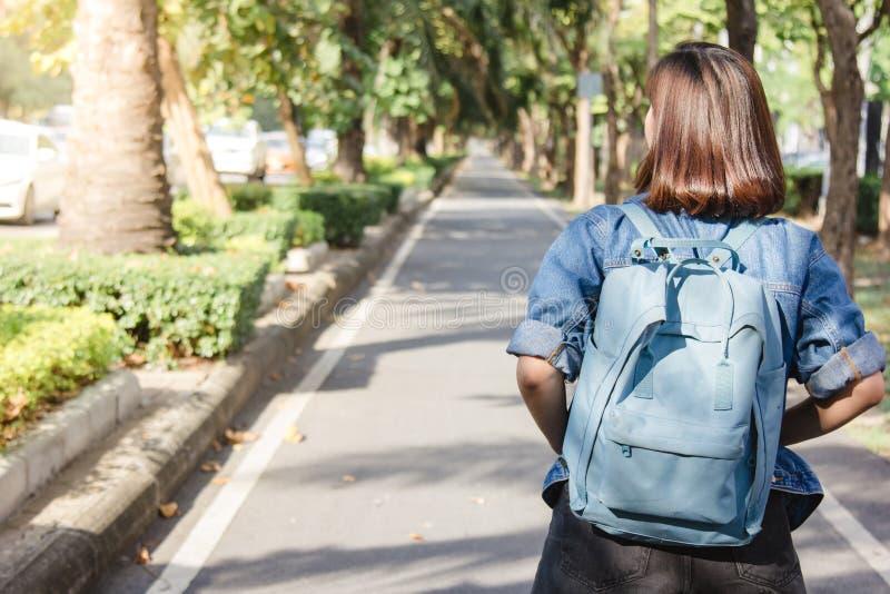 夏天走在街道上的年轻旅游亚裔妇女生活方式画象,运载背包 库存照片