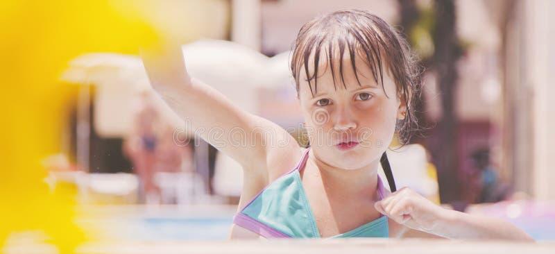 夏天逗人喜爱的小孩女孩画象获得乐趣在水池在好日子 库存照片