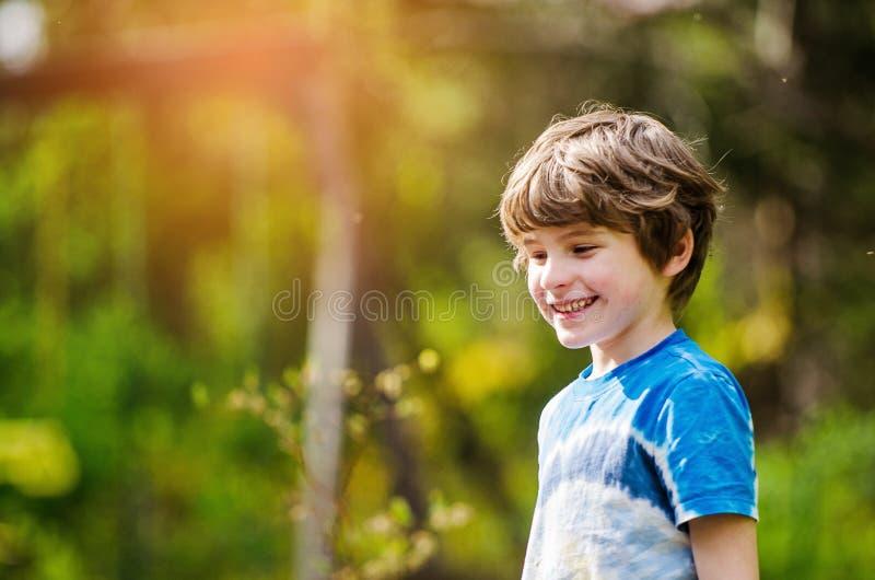 夏天阳光明媚的日子,男孩在外面笑 免版税图库摄影