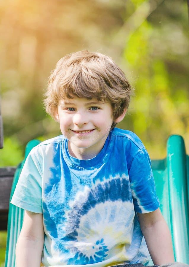 夏天阳光明媚的日子,男孩在滑梯上微笑 免版税库存照片
