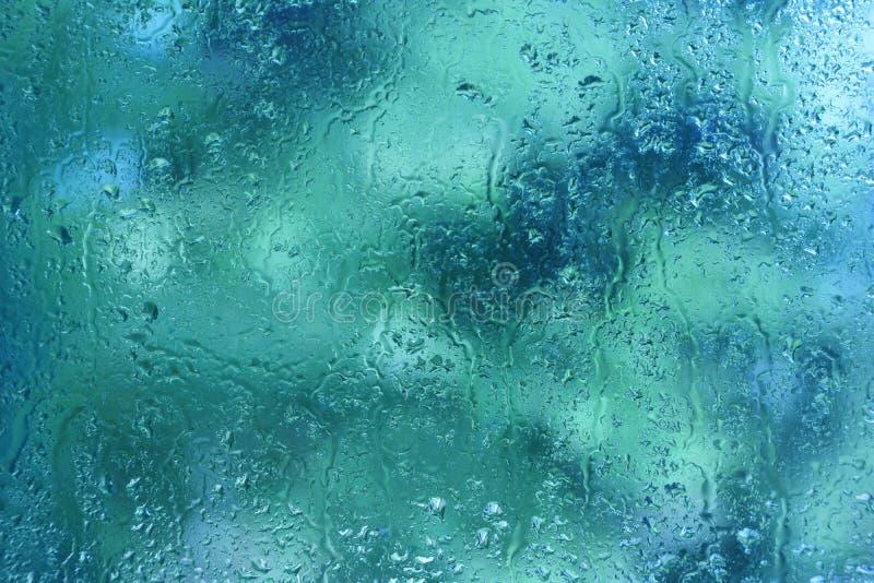 夏天雨在玻璃窗背景纹理滴下 免版税库存图片