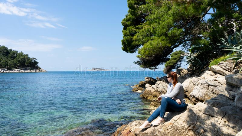 夏天震动女孩画象 看在亚得里亚海的年轻俏丽的妇女,坐峭壁 r 红色顶头马尾 库存照片